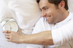 Man Relaxing In Bed With Alarm Clock Kuvituskuvat