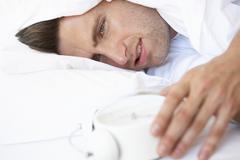 Grumpy Man In Bed Turning Off Alarm Clock Stock Photos
