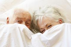 Senior Couple Relaxing In Bed Hiding Under Sheets - stock photo