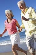 Senior Couple Running Along Beach Together - stock photo