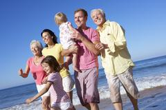 Multi Generation Family Running Along Beach Together Stock Photos