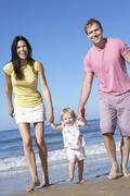Family With Young Daughter Walking Along Beach Together - stock photo