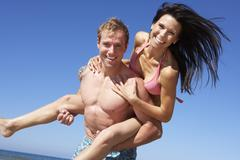 Couple Having Fun On Beach Holiday Together Stock Photos