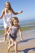 Mother Chasing Daughter Along Beach Stock Photos