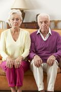 Serious Looking Senior Couple Sitting On Sofa At Home - stock photo