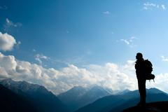 Climbing young adult at the top of summit - stock photo