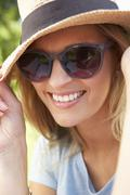 Head And Shoulders Portrait Of Smiling Woman With Sun Hat - stock photo