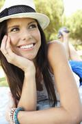 Smiling Woman Lying On Grass Wearing Sun Hat - stock photo