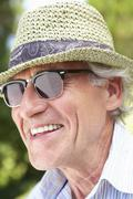 Head And Shoulders Portrait Of Smiling Senior Man With Sun Hat - stock photo