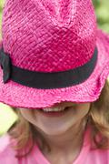 Head And Shoulders Portrait Of Girl Wearing Pink Straw Hat - stock photo