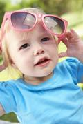Female Toddler Trying To Put On Sunglasses Stock Photos
