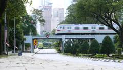 Motorbike and car traffic on Jalan Parlimen, electric train pass railroad bridge Stock Footage