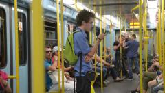 Passenger riding the subway in Milan standing with mobile phone in hand - stock footage