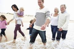 Multi Generation Family Walking Along Beach Together - stock photo