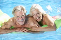 Senior Couple On Holiday In Swimming Pool Stock Photos