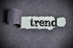 trend word under torn black sugar paper - stock photo