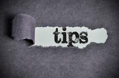 Tips word under torn black sugar paper Stock Photos