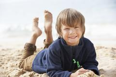 Young Boy Relaxing On Beach - stock photo