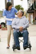 Carer Pushing Disabled Senior Man In Wheelchair Stock Photos