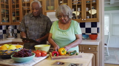 Senior black couple cooking together in kitchen - stock footage