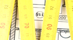 Stock Video Footage of Yellow folding rule on building plan, rotation, close up