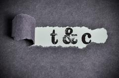 T&C word under torn black sugar paper Stock Photos