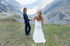 Married couple taking a walk in nature, admiring the beauty of mountains. Stock Photos