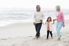 Grandparents Walking Along Beach With Granddaughter - stock photo