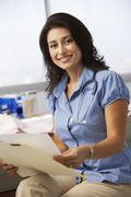 Female Doctor In Surgery Reading Patient Notes - stock photo