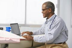 Male Doctor In Surgery Using Laptop - stock photo