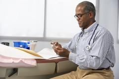 Male Doctor In Surgery Using Mobile Phone Stock Photos