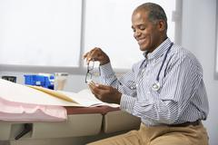 Male Doctor In Surgery Using Mobile Phone - stock photo