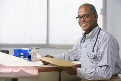 Male Doctor In Surgery Reading Patient Notes Stock Photos