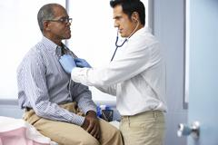 Doctor In Surgery Listening To Male Patient's Chest Stock Photos