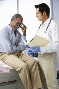 Doctor In Surgery With Male Patient Reading Notes Stock Photos