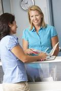 Female Patient With Receptionist In Doctors Waiting Room - stock photo