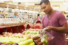Man At Fruit Counter In Supermarket - stock photo