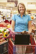 Woman Pushing Trolley By Fruit Counter In Supermarket Stock Photos