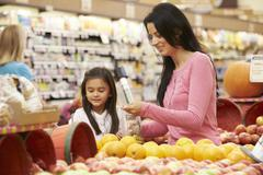 Mother And Daughter At Fruit Counter In Supermarket - stock photo