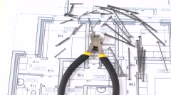Wire cutters with yellow, gray handle on building plan, scheme, among nails Stock Footage