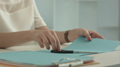 Girl is cutting color blue paper with scissors Stock Footage
