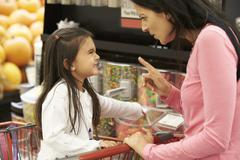 Girl Having Argument With Mother At Candy Counter In Supermarket Stock Photos