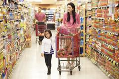 Mother And Daughter Walking Down Grocery Aisle In Supermarket - stock photo