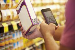 Man Scanning Voucher Code In Supermarket With Mobile Phone Kuvituskuvat