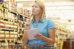 Woman In Grocery Aisle Of Supermarket With List - stock photo