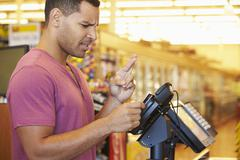 Hopeful Customer Paying For Shopping At Checkout With Card Crossing Fingers Stock Photos