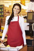 Female Cashier At Supermarket Checkout - stock photo