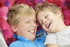 Two Young Boys Relaxing In Garden Hammock Together - stock photo