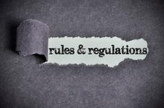 Stock Photo of regulations word under torn black sugar paper