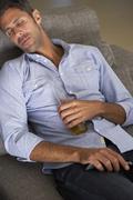 Hispanic Man Fallen Asleep On Sofa Watching TV Stock Photos